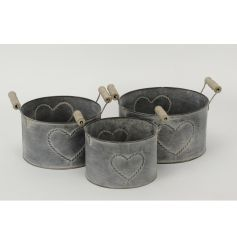 A set of 3 round grey planters with twin wooden handles and a chic heart pattern.