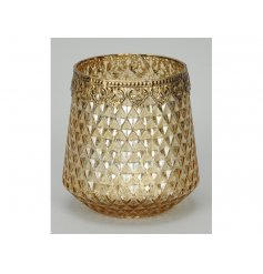 A glamorous cut glass gold candle holder, complete with an ornate metal trim.