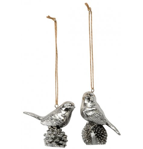 Elegant Christmas birds perched upon pinecones. Complete with an antique inspired silver finish and jute string hangers.