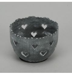 A rustic grey t-light holder with cut out heart designs.