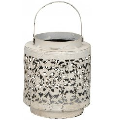 A vintage distressed looking lantern with a cut out floral pattern