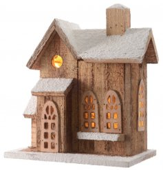 An LED light up wooden house with faux snowy roof