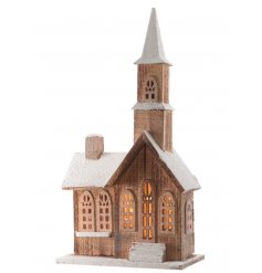 An LED wooden church decoration with faux snowy roof