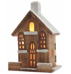 A wooden firewood house decoration with cur out windows and LEDs inside