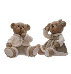 A mix of 2 charming boy and girl sitting ornaments with a touch of festive sparkle.
