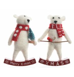 A mix of 2 adorable felt polar bear decorations sat upon a wooden rocking XMAS sign.