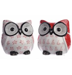 An assortment of 2 ceramic owls in red and white colours. Each has a star and tree design.