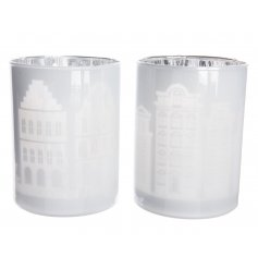 A mix of two white and silver glass t-light holders each with a laser cut house design.
