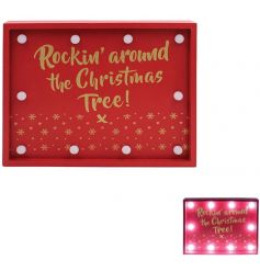 A bright red wooden plaque with a golden script christmas quote and LED surrounding lights
