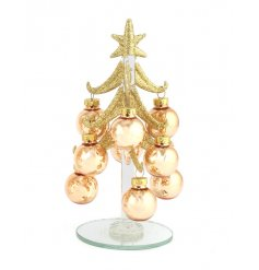 A small glitzy gold Christmas tree table decoration with oversized silver baubles.