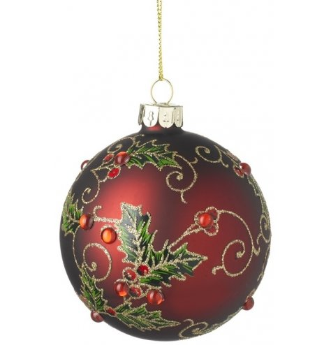 A luxurious rich red bauble with gold glitter swirls and decorative holly leaves, complete with red sequin berries.