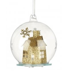 A glass bauble with gold house and LED inside