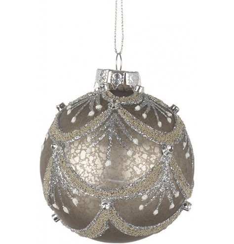 An ornate glass bauble with a mottled antique finish, decorated with an intricate glitter and sequin design.