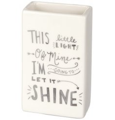 A ceramic based rectangle shaped vase with a silver script song quote