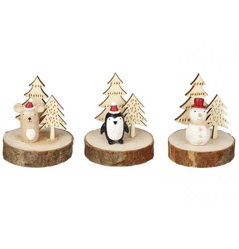 Miniature Christmas character scenes set upon rustic wooden bark bases.