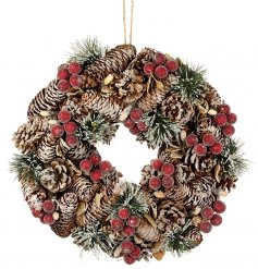 A luxurious pinecone and red berry wreath with a frosted finish.