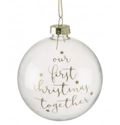 "A beautifully delicate clear glass baubles finished with a golden script ""Our First Christmas Together"""