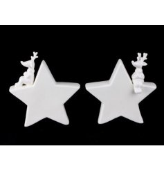 An assortment of 2 ceramic sitting reindeers on stars