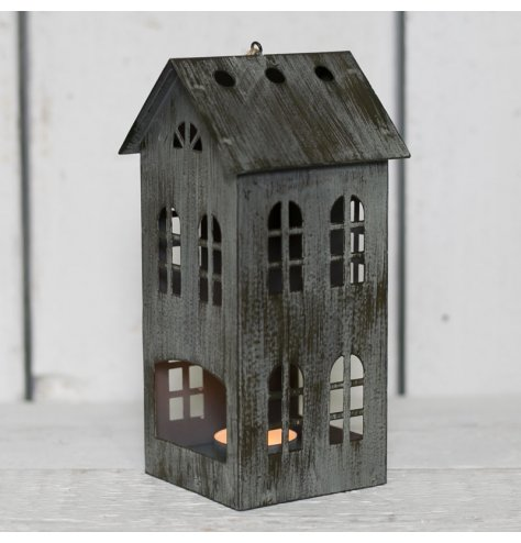 A charcoal grey distressed metal T-light holder in the shape of a house with heart cut out.