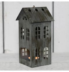 Set with worn down grey walls, this house shaped lantern will bring a delicate glow wherever it goes