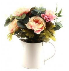 A sweet bouquet of artificial roses perfectly placed in cream metal jug