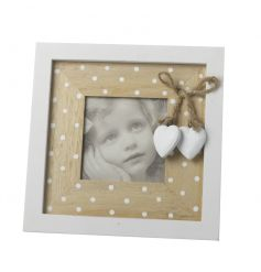 A charming white and natural photo frame with a polka dot design and hanging hearts.