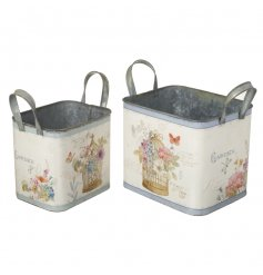 A set of two square planters with handles. Each is decorated with a vintage birdcage and floral design.