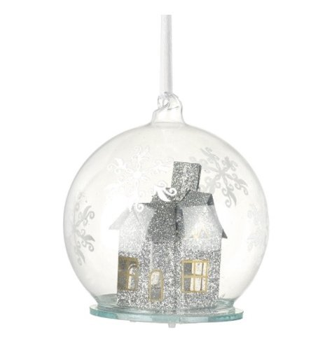 A clear glass bauble decorated with glitter snowflakes on the outside. Inside discover a silver glitter light up house.