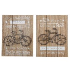 An assortment of 2 unique wooden slogan signs with string bicycle art.