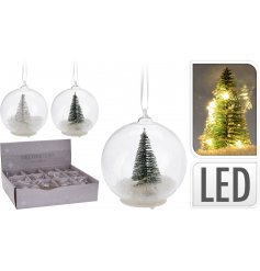 An assortment of 2 glass baubles with a white and green tree, artificial snow and LED lights.