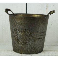 A large copper round planter with heart design