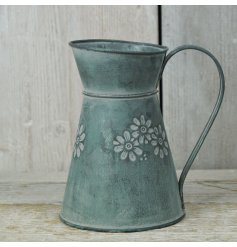 An aged metal zinc jug with embossed flowers
