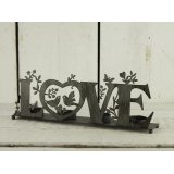 A grey iron tealight holder spelling love