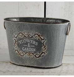 A beautifully distressed themed zinc planter, finished in a grey vintage tone with a 'flowers and garden' script