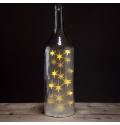 A stylish purple glass bottle with fitted warm glowing led lights
