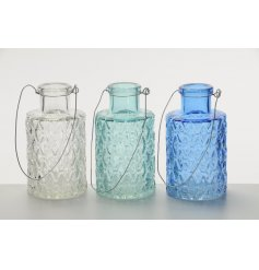 An assortment of 3 glass vases with metal handle