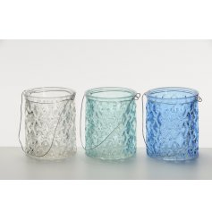 A mix of 3 blue, green and clear textured glass t-light holders with a wire handle.