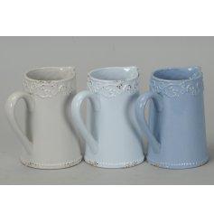 An assortment of pastel toned ceramic jugs,