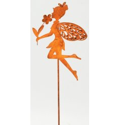 A rusted fairy holding a flower garden stake