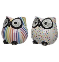 A mix of two colourful rainbow design owl money boxes in stripe and polka dot design.