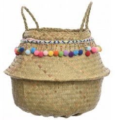 A woven grass storage basket with pompoms
