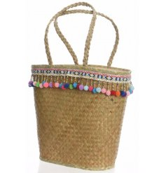 A woven seagrass shopper bag with colourful pompoms