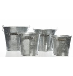 A set of 4 metal buckets with wood handles