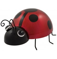 A hand painted red ladybird metal garden decoration