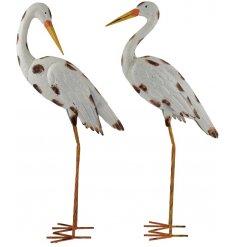 An assortment of 2 hand painted metal stork garden figures