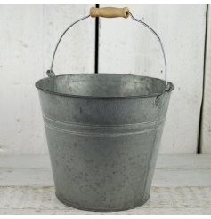 A grey zinc bucket with wood handle planter