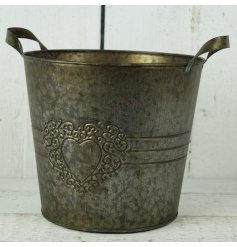 A round copper planter with heart design
