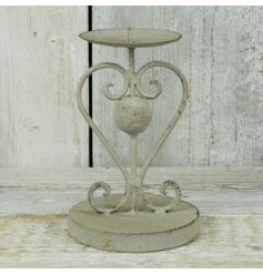 A metal candle holder in rustic grey finish