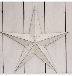 An XL sized metal barn star in an off white tone and complimented with a distressed setting