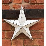A medium sized white washed rough luxe metal barn star.